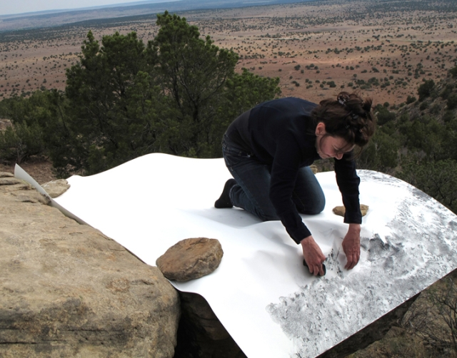 "Artist Jill O'Bryan creating ""frottage"" drawing in the desert landscape of New Mexico."